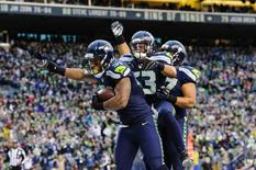 Dec 28, 2014; Seattle, WA, USA; Seattle Seahawks outside linebacker Bruce Irvin (51) and Seattle Seahawks outside linebacker Malcolm Smith (53) and Seattle Seahawks defensive tackle Jordan Hill (97) celebrate after Irvin scored a touchdown against the St. Louis Rams during the second half at CenturyLink Field. Seattle defeated St. Louis 20-6. Steven Bisig-USA TODAY Sports
