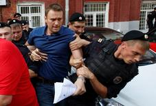 "Policemen detain Russian opposition leader and anti-corruption blogger Alexei Navalny (C), after he visited the city's election commission office to submit documents to get registered as a mayoral election candidate, in Moscow July 10, 2013. Protest leader Alexei Navalny said on July 5 he would destroy the political system under President Vladimir Putin that was ""sucking the blood out of Russia"", after state prosecutors demanded he be jailed for six years on theft charges. Other opposition figures say the trial is intended to prevent Navalny from fulfilling his dream of becoming president and, before that, running for Moscow mayor in September. Navalny was detained on a charge of organizing an unsanctioned rally near the city's election commission office and was then released in less than half an hour. REUTERS/Grigory Dukor (RUSSIA  - Tags: POLITICS CRIME LAW ELECTIONS CIVIL UNREST) - RTX11IQ9"