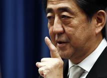 Le Premier ministre japonais Shinzo Abe. La coalition gouvernementale japonaise a approuvé mardi un projet de réduction progressive de l'impôt sur les sociétés au cours des années à venir, censée améliorer la rentabilité des entreprises et favoriser la progression des salaires et la croissance. /Photo prise le 24 décembre 2014/REUTERS/Thomas Peter