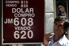 Imagen de archivo de un panel con precios de cotización de dólar y peso chileno en una casa de cambios en Santiago, oct 9 2008. El peso chileno se depreció un 13,1 por ciento frente el dólar este año, ubicándose entre las mayores caídas de los mercados emergentes, una tendencia que podría seguir en 2015 ante una esperada alza de tasas de interés en Estados Unidos y un mayor estímulo monetario local. REUTERS/Ivan Alvarado