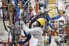 Una empleada trabaja en una línea de producción en una fábrica de automóbiles en Dalian. Imagen de archivo, 18 octubre, 2014. La actividad del sector manufacturero de China se contrajo por primera vez en siete meses en diciembre, mostró el miércoles un sondeo privado, subrayando la urgencia detrás de una serie de sorpresivas medidas expansivas adoptadas por Pekín en los últimos dos meses. REUTERS/Stringer