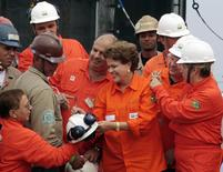 Brazil's President Dilma Rousseff (C) signs an autograph on the hard hat of an employee of Brazilian oil giant Petrobras during the opening ceremony of the P-56 oil rig at Angra dos Reis, near Rio de Janeiro, in this file picture taken June 3, 2011.  REUTERS/Sergio Moraes/Files