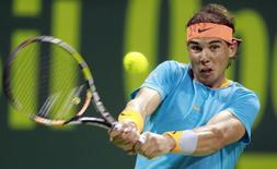 Rafael Nadal of Spain returns the ball to Michael Berrer of Germany during their match at the Qatar Open tennis tournament in Doha January 6, 2015. REUTERS/Mohammed Dabbous