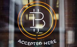 A Bitcoin sign is seen in a window in Toronto, May 8, 2014.    REUTERS/Mark Blinch