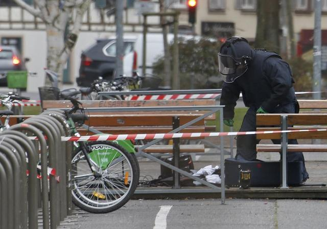 A French policemen inspects an abandoned suitcase in front of a building of Strasbourg's university, January 8, 2015, the day after a shooting at the Paris offices of Charlie Hebdo. REUTERS/Vincent Kessler