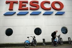Un hombre libera una bicicleta en las afueras de una sucursal de Tesco en Londres, 8 enero, 2015. La mayor cadena de supermercados de Reino Unido, Tesco, planea recortar cientos de millones de libras en costos y vender activos en respuesta a la mayor crisis en sus 95 años de historia.  REUTERS/Luke MacGregor