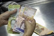 Una cajera cuenta bolívares en un supermercado en Caracas, sep 9 2014. La deuda venezolana se recuperaba el jueves ante un alza de los precios del petróleo, que en la jornada lograron superar los 51 dólares por barril impulsados por una inesperada caída en las existencias de crudo de Estados Unidos. REUTERS/Carlos Garcia Rawlins