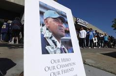"""A picture of former San Diego Chargers and NFL linebacker Junior Seau is displayed as fans (rear) arrive at Qualcomm Stadium to participate in a """"Celebration of Life"""" memorial, held in Seau's memory in San Diego, California May 11, 2012. REUTERS/Mike Blake"""