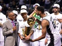 Jun 15, 2014; San Antonio, TX, USA; San Antonio Spurs forward Tim Duncan (21) takes the Larry O'Brian Trophy from guard Tony Parker (9) as he does a TV interview with ESPN announcer Stuart Scott after game five of the 2014 NBA Finals against the Miami Heat at AT&T Center. Bob Donnan-USA TODAY Sports