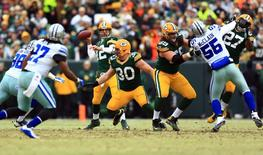 Jan 11, 2015; Green Bay, WI, USA; Green Bay Packers quarterback Aaron Rodgers (12) throws a pass against the Dallas Cowboys in the first quarter in the 2014 NFC Divisional playoff football game at Lambeau Field. Mandatory Credit: Andrew Weber-USA TODAY Sports
