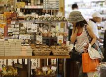 Женщина в супермаркете в Токио 29 июля 2014 года. Правительство Японии ожидает, что экономика вырастет в реальном выражении на 1,5 процента в 2015 бюджетном году с учетом колебаний цен благодаря ожидаемому ускорению потребительских расходов. REUTERS/Yuya Shino