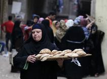 A woman walks away after buying bread at a bakery in Cairo, January 8, 2015. REUTERS/Mohamed Abd El Ghany
