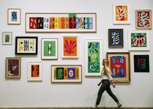 """An employee poses with paper cut outs from the """"Henri Matisse: The Cut-Outs"""" exhibition at the Tate Modern gallery in London, in this file photo taken April 14, 2014.   REUTERS/Luke MacGregor/Files"""