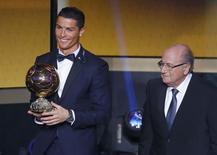 Real Madrid's Cristiano Ronaldo of Portugal, holds his World Player of the Year trophy as he stands next to FIFA President Sepp Blatter (R) during the FIFA Ballon d'Or 2014 soccer awards ceremony at the Kongresshaus in Zurich January 12, 2015.   REUTERS/Ruben Sprich