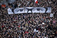 """Manifestantes exibem painéis para recriar os olhos do editor do jornal Charlie Hebdo, Stephane Charbonnier, conhecido como """"Charb"""", durante uma marcha de centenas de milhares de pessoas em Paris, na França, no domingo. 11/01/2015 REUTERS/Charles Platiau"""