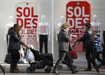 People walk past a clothing store window with discount signs in Strasbourg, during the first day of winter sales in France, January 7, 2015.   REUTERS/Vincent Kessler