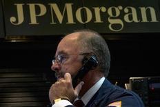 Un operador de JPMorgan Chase trabaja en el stand de la compañía en la bolsa de Nueva York. Imagen de archivo, 28 agosto, 2014.  JPMorgan Chase & Co, el mayor banco de Estados Unidos por activos, reportó el miércoles una caída de 6,6 por ciento en sus ganancias trimestrales, golpeado por unos costos legales de casi 1.000 millones de dólares y una mayor cantidad de fondos reservados para cubrir préstamos incobrables. REUTERS/Brendan McDermid