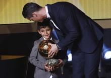 Real Madrid's Cristiano Ronaldo of Portugal, stands with his son Cristiano Ronaldo Jr, after winning the FIFA Ballon d'Or 2014 during the soccer awards ceremony at the Kongresshaus in Zurich January 12, 2015.                                 REUTERS/Arnd Wiegmann