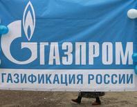 Плакат с логотипом Газпрома на церемонии по случаю окончания работ по газификации аула Али-Кую в Ставропольском крае. 14 ноября 2012 года. Российский монополист в экспорте природного газа - Газпром по итогам 2014 года на 9 процентов в унисон снизил экспорт в дальнее зарубежье и добычу, объем которой стал рекордно низким, следует из предварительных данных концерна. REUTERS/Eduard Korniyenko