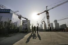 Site de construction à Pékin. La croissance économique mondiale sera au mieux modeste cette année en raison de la persistance d'une inflation faible, selon plusieurs enquêtes de Reuters réalisées auprès d'économistes, et les difficultés de la zone euro et de la Chine risquent de peser sur la tendance globale. /Photo prise le 29 décembre 2014/REUTERS/Jason Lee