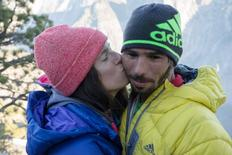 Climber Kevin Jorgeson (R) is kissed by his girlfriend Jacqui Becker after Jorgeson and climber Tommy Caldwell (not pictured) completed the first free climb ascent of El Capitan's Dawn Wall in Yosemite National Park, California in this January 14, 2015 handout photograph. REUTERS/Ted Distel/Adidas Outdoor/Handout via Reuters