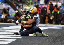 Seattle Seahawks wide receiver Jermaine Kearse (15) catches a 35 yard pass from quarterback Russell Wilson (not pictured) for the game winning touchdown ahead of Green Bay Packers cornerback Tramon Williams (38) during the overtime period in the NFC Championship game at CenturyLink Field. Mandatory Credit: Kyle Terada-USA TODAY Sports