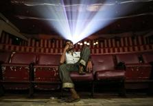 """A cinema goer watches Bollywood movie """"Dilwale Dulhania Le Jayenge"""" (The Big Hearted Will Take the Bride), starring actor Shah Rukh Khan, inside Maratha Mandir theatre in Mumbai December 11, 2014.  REUTERS/Danish Siddiqui"""