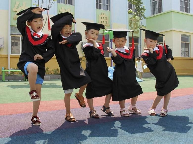 Children In Gowns And Mortarboards Pose For Pictures During Their Kindergarten Graduation Ceremony Wenxian