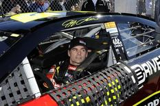 NASCAR Sprint Cup Series driver Jeff Gordon, of the number 24 car, prepares to exit his car after his outside pole-securing run during qualifying for the Daytona 500, at Daytona International Speedway in Daytona Beach, Florida, February 17, 2013. REUTERS/Brian Blanco