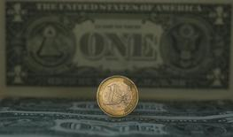 Монета валюты евро на фоне долларовой купюры в Мадриде 17 ноября 2011 года. Курс евро к доллару упал до 11-летнего минимума, после того как Европейский центробанк объявил о намерении предоставить рынку свыше 1 триллиона евро в ходе скупки гособлигаций. REUTERS/Sergio Perez