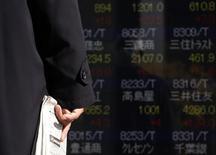Мужчина у брокерской конторы в Токио. 19 декабря 2014 года. Азиатские фондовые рынки выросли в пятницу благодаря активным действиям Европейского центробанка по стимулированию экономики еврозоны. REUTERS/Yuya Shino