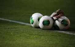 Мячи и вратарские перчатки перед тренировкой бразильской сборной на стадионе в Бразилиа. 14 июня 2013 года. REUTERS/Kai Pfaffenbach