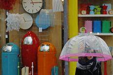 A woman carrying an umbrella passes a shop selling brightly coloured household items in Brighton southern England January 8, 2015.    REUTERS/Luke MacGregor