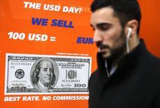 Человек проходит мимо пункта обмена валюты в Мадриде 15 января 2015 года. Индекс доллара к корзине шести основных валют снизился с 11-летнего максимума после выхода макроэкономической статистики США и разочаровавших рынок квартальных отчетов крупных американских компаний. REUTERS/Andrea Comas