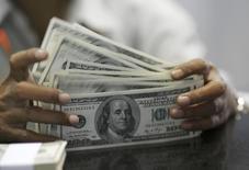 Работник пункта обмена валюты считает доллары. Джакарта, 19 ноября 2008 года. Крупнейшая российская нефтекомпания Роснефть должна погасить около $7,14 миллиарда из двухлетнего кредита международных банков 13 февраля 2015 года, сообщили близкие к сделке банкиры. REUTERS/Beawiharta