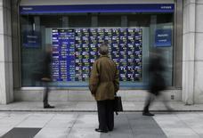 Un hombre observa una pantalla que muestra índices económicos en Tokio. Imagen de archivo, 6 enero, 2015. Las bolsas de Asia vacilaba entre territorio positivo y negativo el viernes, en momentos en que un repunte tardío en Wall Street ayudaba a contrarrestar las preocupaciones sobre el crecimiento global y la debilidad de las acciones chinas. REUTERS/Issei Kato