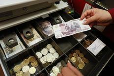 """Кассир держит в руках 500-рублевую купюру в магазине Винотека в Красноярске 2 февраля 2015 года. Рубль существенно растет во вторник на фоне дорожающей нефти, чья динамика перебивает сейчас негативные факторы: увеличение внешней долговой нагрузки и угрозу новых западных санкций против России в феврале, """"мусорный"""" рейтинг S&P и риски изменения до этого статуса рейтингов другими агентствами. REUTERS/Ilya Naymushin"""
