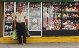 Una persona frente a una tienda en Quito, nov 5 2014. Colombia y Ecuador acordaron desmontar durante febrero una salvaguardia cambiaria impuesta por Quito a inicios de año para proteger su economía dolarizada, a fin de evitar un deterioro en el comercio binacional, dijo el jueves un funcionario ecuatoriano.  REUTERS/Guillermo Granja