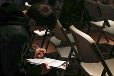 A man fills out paperwork before a screening session for seasonal jobs at Coney Island in the Brooklyn borough of New York March 4, 2014.  REUTERS/Shannon Stapleton