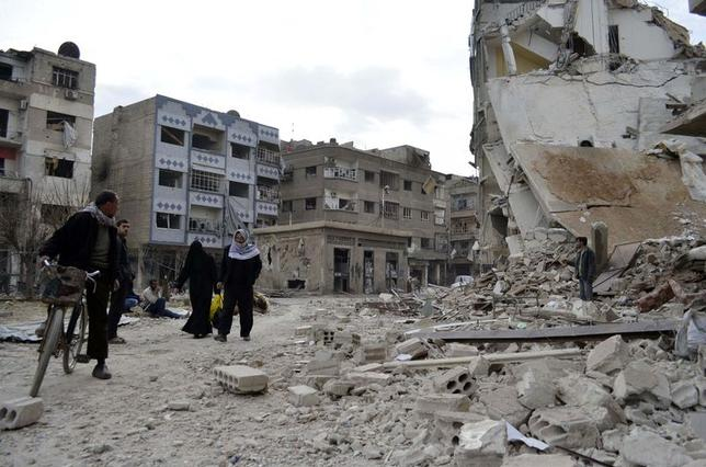 Residents walk past damaged buildings after what activists said were air strikes by forces loyal to Syria's President Bashar al-Assad in the Douma neighborhood of Damascus February 6, 2015. REUTERS/Amer Almohibany
