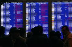 Пассажиры у информационного табло в аэропорту Домодедово. 28 декабря 2010 года. Перевозки авиапассажиров в РФ выросли в прошлом году на 10,2 процента до 93,18 миллиона человек, сообщило в понедельник Федеральное агентство воздушного транспорта (Росавиация). REUTERS/Mikhail Voskresensky
