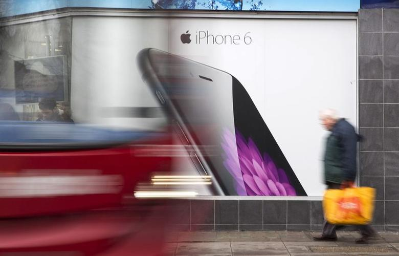A bus and pedestrian pass an advertisement for the Apple iPhone 6 in north London January 28, 2015. REUTERS/Neil Hall