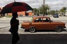 A woman walks past a Moskvich car in front of Fabian Zakharov's Zakharov Auto Parts shop in Hialeah, Florida, February 4, 2015. REUTERS/Javier Galeano