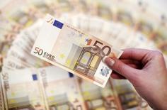 Сотрудник банка держит в руках купюру евро в Сараево 19 марта 2012 года. Курс евро снижается, поскольку министры финансов еврозоны не смогли договориться с Грецией об условиях кредитования. REUTERS/Dado Ruvic