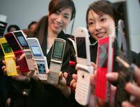 Imagen de archivo de modelos mostrando teléfonos celulares plegables en Tokio. 16 enero, 2007. Los despachos en Japón de teléfonos plegables -con dos secciones y una bisagra- aumentaron en 2014 por primera vez en siete años, mientras que las ventas de aparatos inteligentes cayeron, lo que pone de relieve el apego de los consumidores a los modelos más antiguos y menos costosos. REUTERS/Toshiyuki Aizawa