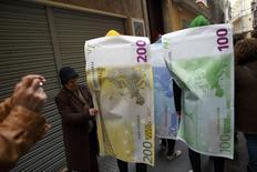 Участники карнавала в Кадисе в костюмах в виде банкнот евро. 16 февраля 2015 года. Евро восстановился во вторник после утреннего спада, благодаря улучшению настроений немецких инвесторов и надеждам на то, что Греция добьется от партнеров по еврозоне поддержки вне рамок действующей программы помощи. REUTERS/Marcelo del Pozo