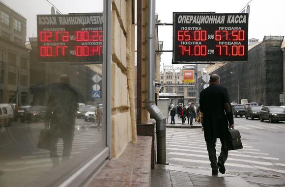 A man walks under a board displaying currency exchange rates in Moscow, February 12, 2015. REUTERS/Maxim Zmeyev