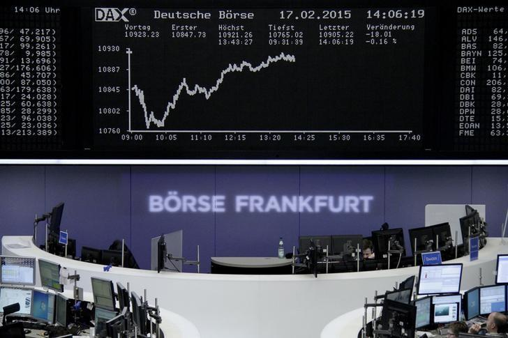 Traders are pictured at their desks in front of the DAX board at the Frankfurt stock exchange February 17, 2015.      REUTERS/Staff