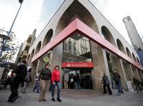 Unas personas pasan frente a una sucursal del banco Santander en el centro de Montevideo, jun 4 2010. Uruguay, con calificaciones de grado inversor Baa2/BBB-/BBB-, está reabriendo su mayor bono de largo plazo, con vencimiento en 2050 y una tasa del 5,1 por ciento, informó el lunes el Ministerio de Economía y Finanzas.                REUTERS/Andres Stapff