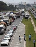 Camioneros bloquean parte de la carretera BR-116 en Curitiba, Brasil, feb 23 2015. Una protesta de camioneros por el alto precio de los combustibles bloqueó el lunes por sexto día la carretera más importante de la principal zona productora de granos de Brasil, amenazando el suministro de diésel para las máquinas que cosechan una campaña de soja que esperan sea récord.  REUTERS/Rododlfo Burher